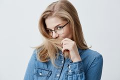 Youth and happiness concept. Beautiful Caucasian teenage girl in denim shirt, looking at the camera with appeal, playing. Youth and happiness concept. Close up Stock Photography