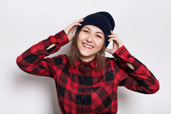 Youth and happiness concept. Pretty teenage girl wearing stylish cap and red checked shirt being happy and smiling holding her han Stock Photo