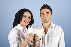 Youth happy couple holding milk glasses. Youth happy couple holding glasses with milk and smiling,they wear white clothes on blue background,check also my Stock Photo