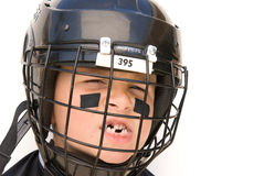 Youth Hockey Player. A young boy shows off his missing teeth while in his hockey gear royalty free stock photography