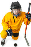 Youth hockey player standing on one knee. Boy in yellow hockey uniform with stick stand in knight position stock image
