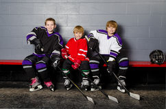 Youth Hockey Players in Dressing Room. Three Youth Boys Hockey Players Pose in Dressing Room in their equipment stock photo
