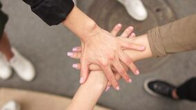 Youth interracial companies lay their hands on top of each other as a sign of support and solidarity. Mass protests in
