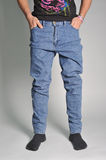 Youth jeans put on the guy. On a guy wearing jeans; view of the waist; guy in the jeans and socks Royalty Free Stock Image