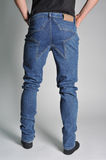 Youth jeans put on the guy. On a guy wearing jeans; view of the waist; guy in the jeans and socks Stock Photos
