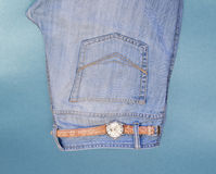 Youth jeans, wrist watch on blue background Royalty Free Stock Photo