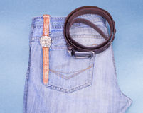 Youth jeans, wrist watches, leather strap on a blue background Royalty Free Stock Images