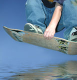 Youth jumping over water. On skateboard deck Stock Photography