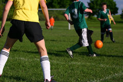 Youth kids soccer game on warm sunny day. Kids on a soccer team work together Royalty Free Stock Photography