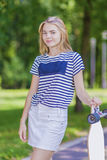 Youth LIfestyle Concepts. Blond Caucasian Teenage Girl Posing With Long Skateboard in Green Forest Stock Photo