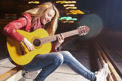 Youth Lifestyle Ideas and Concepts. Young smiling Caucasian Blond Woman Playing The Guitar Outdoors at Night. Stock Images