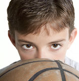 Youth Looking Over Basketball. Young teen peering over the top of a basketball. Isolated on white Royalty Free Stock Photos