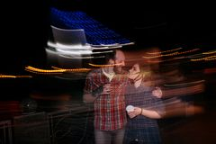 Youth nightlife. Dating couple in motion. Romantic outdoors, blurred lights urban background. Psychedelic emotion, hugging happy people, love concept Royalty Free Stock Images