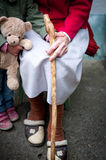 Youth and oldness. Little girl with a teddy bear holding hand of the old lady Royalty Free Stock Image