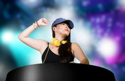 Young attractive and happy Asian Japanese DJ woman remixing using deejay gear and headphones at night club with lights background royalty free stock photos