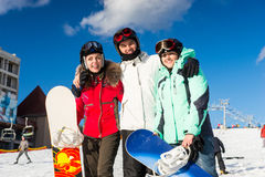 Youth in ski suits and ski goggles having fun while standing wit Stock Photos