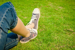 Youth sneakers on girl legs on grass Stock Photos