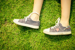 Youth sneakers on girl legs on grass Stock Photography