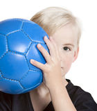 Youth with Soccer Ball. Young (preschool age) boy with blue soccer ball partially hidden behind face Royalty Free Stock Photos