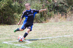Youth Soccer Football Player Kicks the Ball. A young boy kicks the soccer ball during the Breakers Cup Soccer Tournament in Santa Cruz, CA Royalty Free Stock Photos