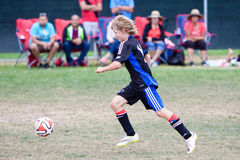 Youth Soccer Football Player Running with the Ball. A young boy chases the soccer ball during the Breakers Cup Soccer Tournament in Santa Cruz, CA Royalty Free Stock Photo