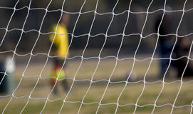 Youth Soccer Game. Soccer game being played, focus is on goal net Royalty Free Stock Photo
