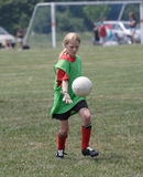 Youth Soccer Player in Action. On field - goalie ready to kick ball Royalty Free Stock Photo