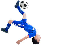 Youth soccer player kicking the ball. Youth asian (thai) soccer player in blue uniform shooting performing a bicycle kick, Isolated on white background Stock Photography