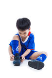 Youth soccer player tying shoe and prepare for competition. Spor. Youth asian (thai) soccer player in blue uniform tying shoe before playing soccer. Child Royalty Free Stock Photo