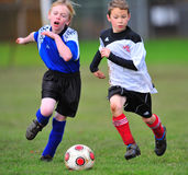 Youth soccer players running after the ball Royalty Free Stock Photo