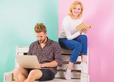 Youth spend leisure preparing for entrance exam. Couple students with book and laptop studying. Man and woman use stock images