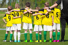Youth sports team. Young players standing together with coach stock photos