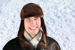 Youth stands in ear-flaps hat. Youth in winter stands on snow in ear-flaps hat and laughs Stock Images