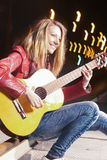 Youth Street Life Concepts. Portrait of Smiling Caucasian Blond Girl Playing the Guitar Outside on Street Royalty Free Stock Photos