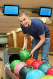 Youth takes ball for playing bowling. Youth bends over to automat and takes  ball for playing bowling Stock Photo