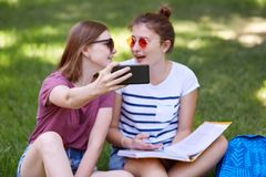 Youth and technology concept. Positive young best female friends sit closely, read book and pose for making selfie portrait, focus. On modern smart phone, pose stock images