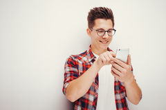 Youth and technology. Studio portrait of man using smart phone. Isolated Royalty Free Stock Photography