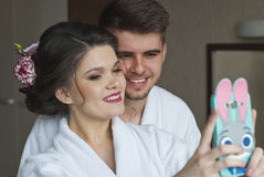 Youth and technology. Young smiling loving couple taking selfie while standing in hotel Stock Photos