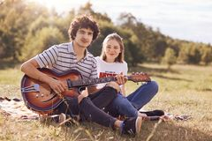 Youth, teenagers and entertainement concept. Handsome male plays guitar and sings songs to his girlfriend, look happily at camera,. Have joyful expressions Stock Images