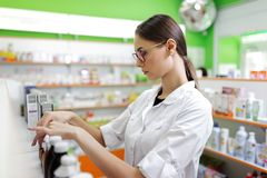A youthful attentive skinny girl with long dark hair and glasses, wearing a medical overall, is adjusting medicines on royalty free stock image