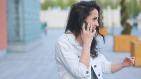 Youthful attractive brown-haired caucasian girl in white jeans coat and black t-shirt talking on the phone, wind swaying stock footage
