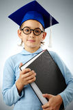 Youthful bachelor. Portrait of cute lad in eyeglasses and student hat with book looking at camera Royalty Free Stock Images