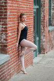 Youthful ballet girl against old building. Beautiful and young ballerina leaning back against red brick wall with serious look Stock Photo