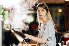 A youthful blonde slim gir,dressed in casual outfit,cleans the coffee machine with steam in a modern coffee shop. royalty free stock photography