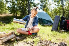 Boy scout. Youthful boy pouring tea in mug while enjoying summer day by campfire on background of his tent Stock Images