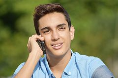 Youthful Colombian Boy Using Cell Phone And Happy. A handsome hispanic male teenager Royalty Free Stock Image