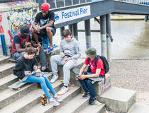 Youthful friends sit on stone steps leading to Thames River, at Royalty Free Stock Images