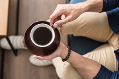 Youthful guy drinking warm beverage at home. Close up of hands of young man holding cup of coffee with saucer. He is sitting on couch near table in his room. Top Stock Photo
