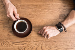 Youthful guy having little break with hot beverage. Close up of hands of young man drinking coffee at kitchen table. He is holding cup by its handle by one hand Stock Photo