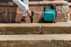 Youthful guy traveling alone around city sights. Close up of legs of young man standing on stairs near wall of old building. His backpack is lying on floor Royalty Free Stock Photos